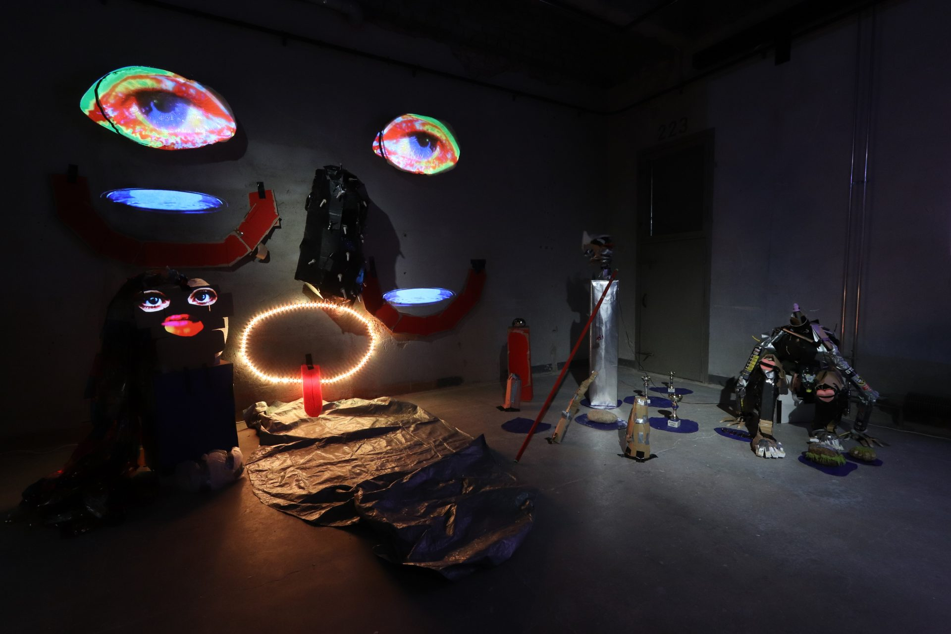 Seinälle heijastetut kasvot ja muita kierrätysmateriaaleista valmistettuja teoksia Sofi Häkkisen näyttelyssä
