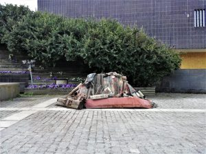 A sculpture made out of recycled material in front of a building