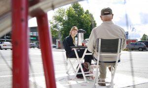 Vanha mies ja nuori nainen istuvat pöydän ääressä tyhjässä parkkiruudussa.