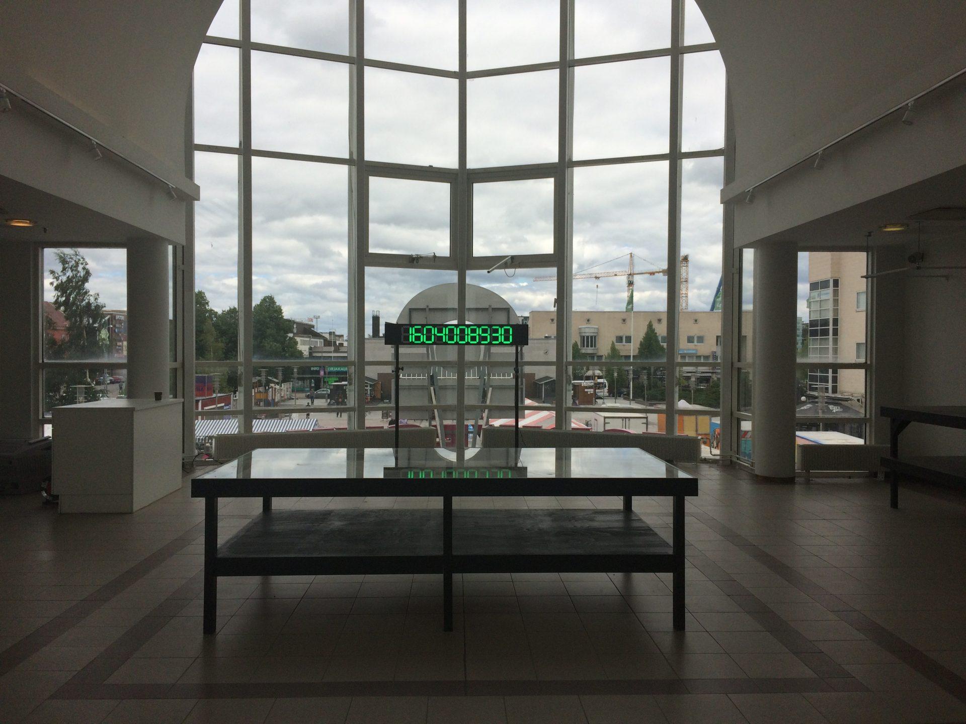 Suuren moniruutuisen ikkunan edessä on pöytä, jonka yläpuolella olevassa digitaalisessa näytössä on kymmenlukuinen numerosarja.